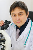 Portrait of male researcher working with microscope — Stock Photo