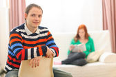 Portrait of young man and girlfriend reading in background — Stock Photo