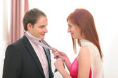 Red hair young woman helping tie necktie — Stock Photo