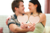 Closeup on Valentines hearts in hands of romantic couple — Stock Photo