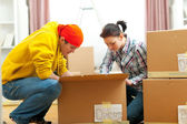 Young couple unpacking in new house — Stock Photo
