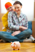 Closeup on piggy bank and young couple in background — Stock Photo