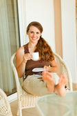 Smiling young woman relaxing on terrace with cup of coffee — Stock Photo
