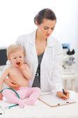 Pediatric doctor skriver något i urklipp — Stockfoto