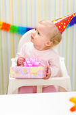Baby with present looking in corner — Stock Photo