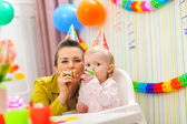 Baby and mother blowing into party horn — Stock Photo