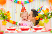 Mother kissing her happy while baby checking present — Stock Photo