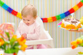 Baby happy and embarrassed receiving birthday cake — Stock Photo