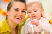 Portrait of mom and baby eating birthday cake — Stock Photo