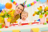 Smiling mom and eat smeared baby on birthday celebration party — Stock Photo