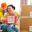 Hugging young couple showing home for sale sign with sold sticke — Stock Photo