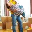 Young couple having fun while moving to new house — Stock Photo
