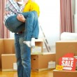 Home for sale sign with sold sticker and guy holding girlfriend — Stock Photo #9831644