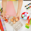 Preparations for Easter. Closeup on hands painting on egg. - Stock Photo