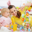 Mother and baby making Easter decoration — Stock Photo #9832125