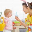 Mother helping baby collecting Easter eggs — Stock Photo #9832130