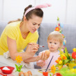 Mother showing baby how to paint on Easter egg — Stock Photo