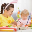 Mother and baby painting on Easter eggs — Stock Photo #9832146