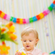 Eat smeared baby eating orange at birthday party — Stock Photo