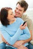 Güzel bir kız bir erkek arkadaşına cep telefonunda gösterilen — Stok fotoğraf