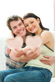 Portrait of happy young couple with porcelain hearts — Stock Photo
