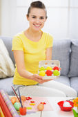 Smiling woman showing tray with colorful Easter eggs — Stock Photo