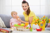 Mother giving baby Easter egg — Stockfoto
