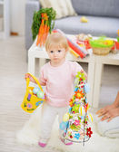 Baby holding basket of Easter eggs and decoration — Stock Photo