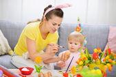 Madre mostrando cariño a pintar el huevo de pascua — Foto de Stock
