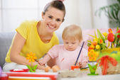 Happy mother helping baby painting on Easter eggs — Stock Photo