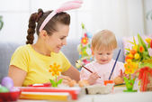 Mother and baby painting on Easter eggs — Stockfoto