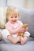 Happy baby eating Easter rabbit cookie — Stock Photo