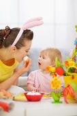 Mother and baby eating Easter egg — Stock Photo