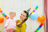 Portrait of happy mom and baby with birthday gift — Stock Photo