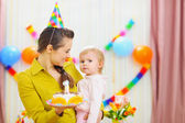 Portrait of baby and mother with birthday party cake — Stock Photo