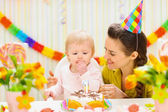 Portrait of happy mom and baby eating birthday cake — Stock Photo
