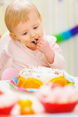 Eat smeared baby eating birthday cake — Stock Photo