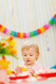 Eat smeared baby eating orange at birthday party — Стоковое фото