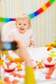 Mother making photos of baby on birthday party — Stock Photo