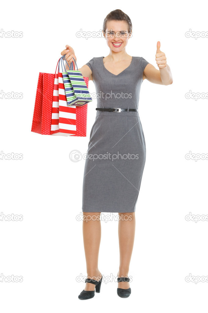 Happy elegant woman with shopping bags showing thumbs up — Stock Photo #9831952