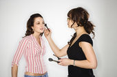 Makeup artist and woman. — Stock Photo