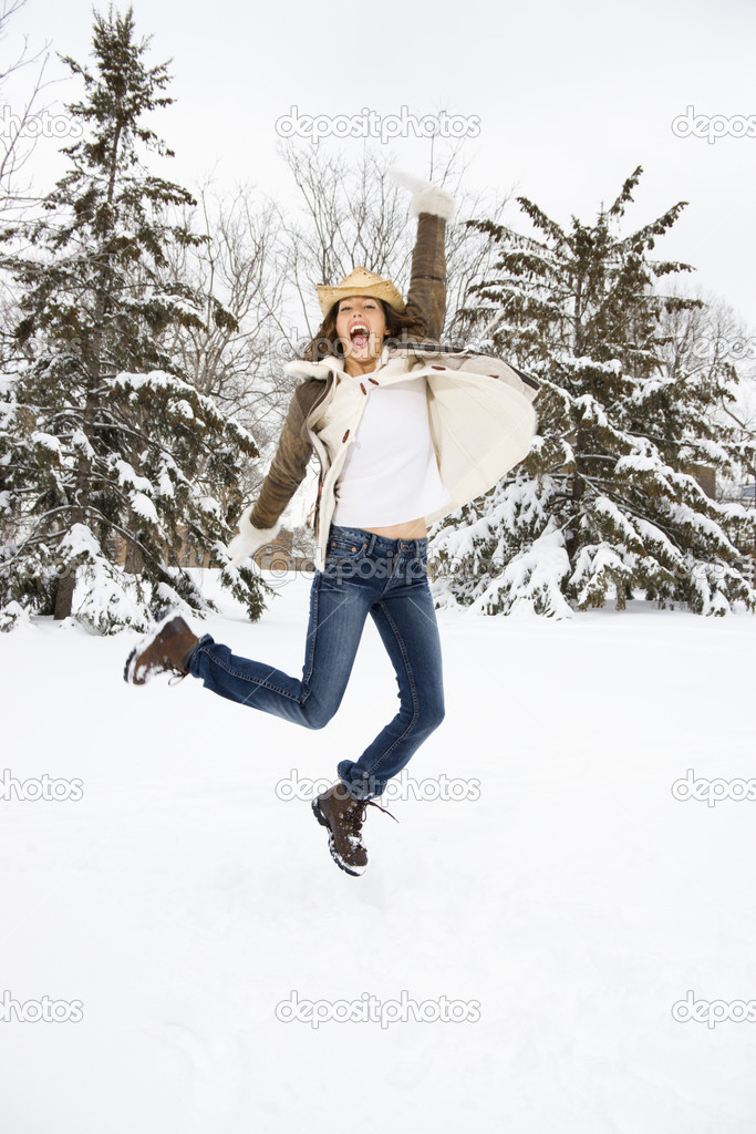 Caucasian young adult female leaping into the air in snowly climate wearing straw cowboy hat. — Stock Photo #9215829