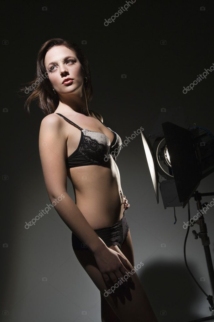 Sexy Caucasian woman in lingerie standing next to spotlight. — Stock Photo #9217018
