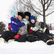 Family sitting in snow. - Foto Stock
