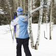 Female walking with skis. — Stock Photo