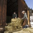 Attractive Couple Moving Hay Bales — Stock Photo #9225952