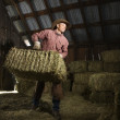 Man in Barn Moving Bales of Hay — Stock Photo #9226001