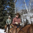 Stock Photo: Man and Woman Riding Horses in the Snow