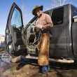 Stock Photo: Man Wearing Cowboy Hat With Lariat and Truck