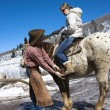 Wrangler helping with horse. - Foto Stock